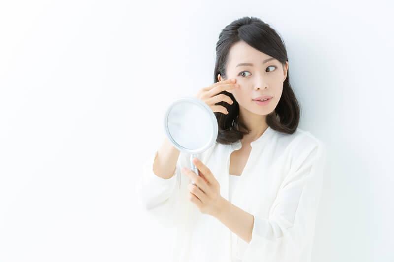 鏡で目元を見る女性
