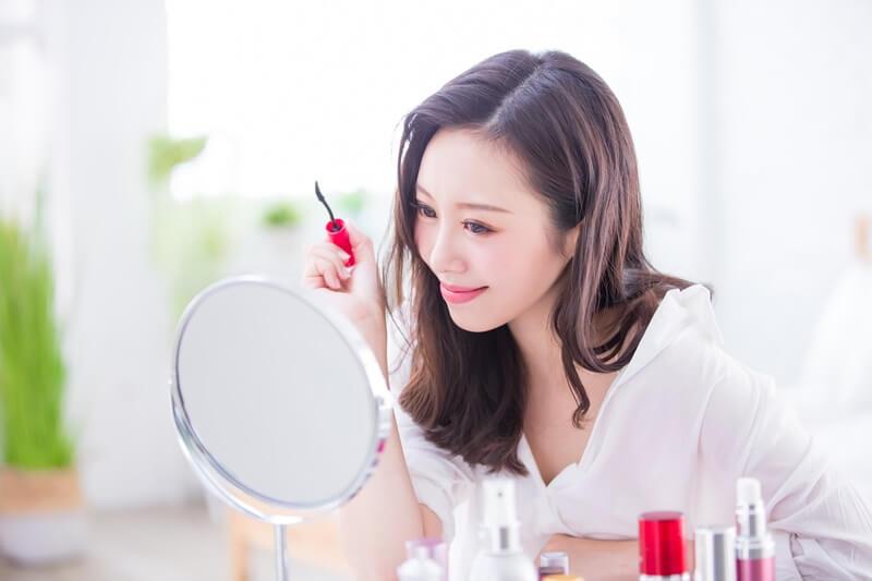 鏡を見てアイメイクをする女性