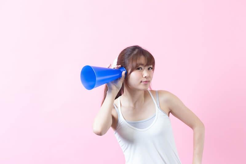 メガホンを耳にあてる女性